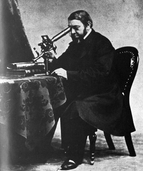A studio portrait of a man seated at a table, looking through a microscope.
