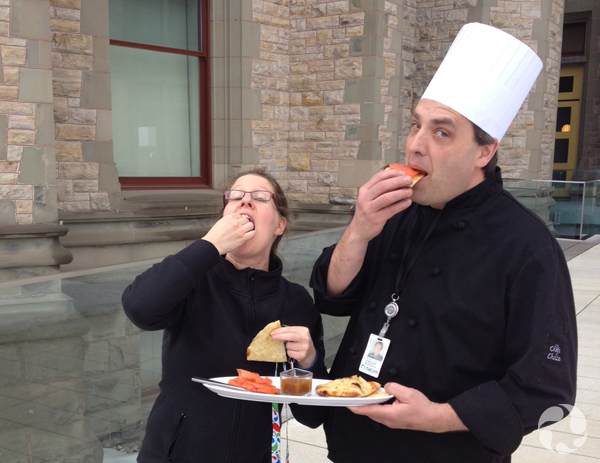 Outside the museum, a man wearing a chef's hat and holding a plate in one hand tastes food with a woman.
