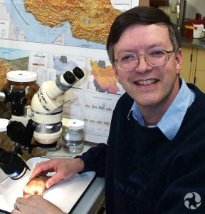 Brian Coad in front of a table with a microscope and a fish.