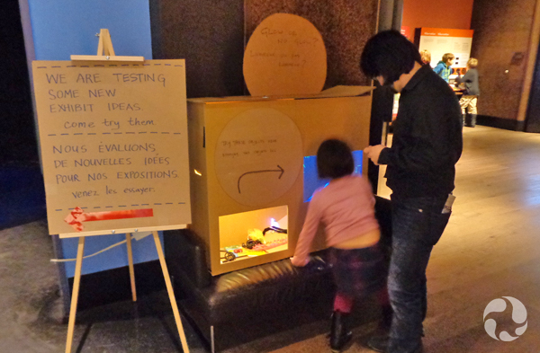 An adult and a child investigate a cardboard mock-up of an interactive.