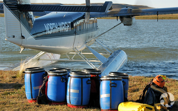 Barrels and gear sit on shore beside a float plane.