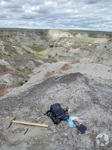 Backpack and rock pick lie on ground at fossil site overlooking the South Saskatchewan River.