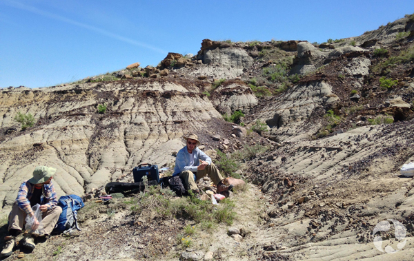 Jordan Mallon and Scott Rufolo sitting on ground amidst the hills of the badlands.