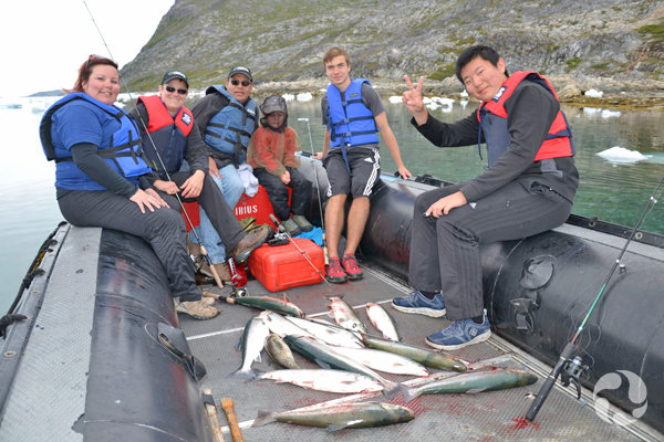 Paula and others sitting on side of Zodiac with fish they have caught.