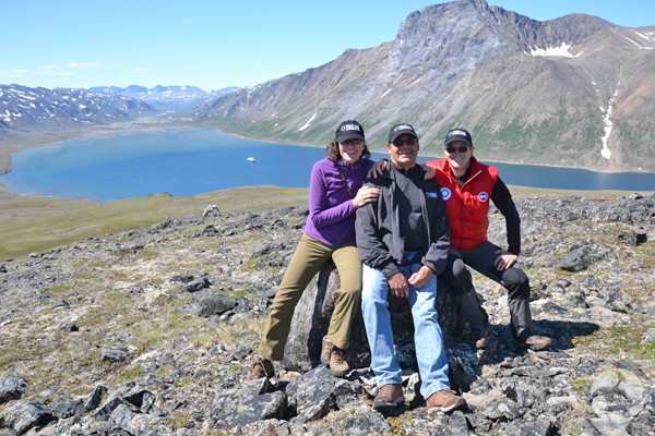 Paula Piilonen with two other participants pose on top of peak overlooking a fiord.
