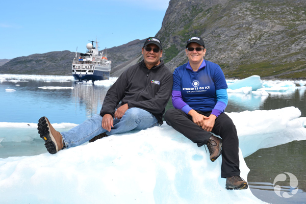 Paula Piilonen and colleague Noel Alfonso sitting on an ice floe in a harbour.