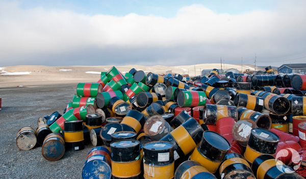 Dozens of fuel drums in a pile.