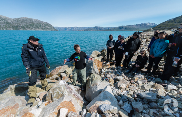 Paula Piilonen and students examine rocks along the shore of the mine site.