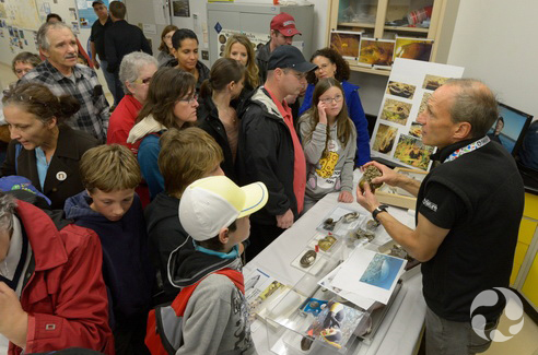 People crowd around a table to hear a scientist talk about mussel biodiversity.