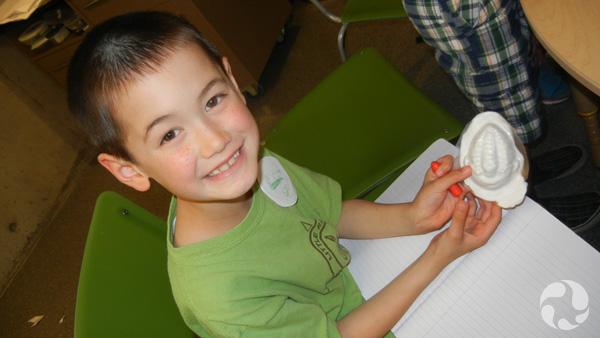 A boy shows his trilobite model.