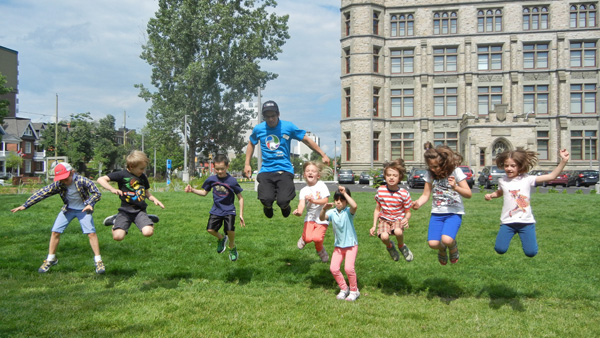 Eight children and their camp counsellor jumping up and down on the museum's west lawn.