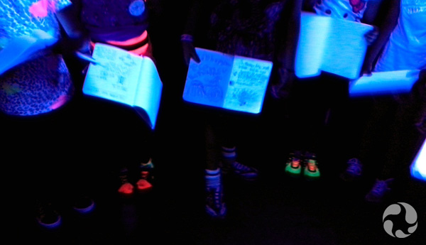 Pages of open notebooks glow under UV light.