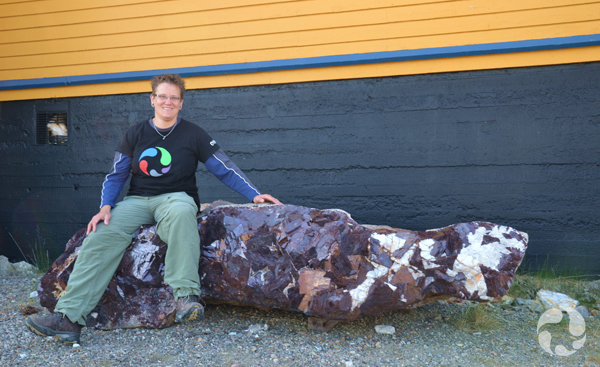 Paula Piilonen sits on a large piece of ore containing cryolite and siderite crystals.