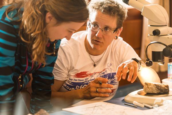 Paula Piilonen talks to student as they sit near microscope.