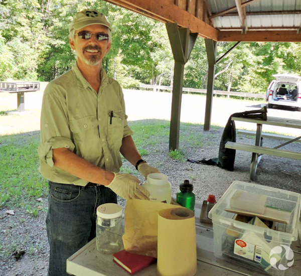 Claude Renaud stands by table upon which lie equipment used to collect lamprey specimens.