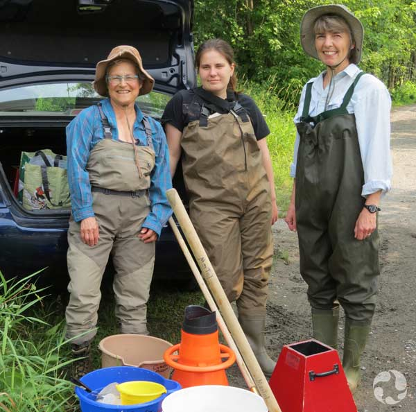 Three women in waders, carrying buckets and nets.
