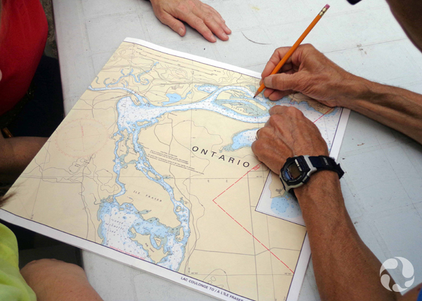 A man's hands indicate a site on a chart.