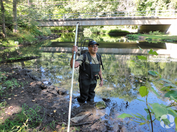 A man in hip waders standing in the muck of the Saw Kill River.