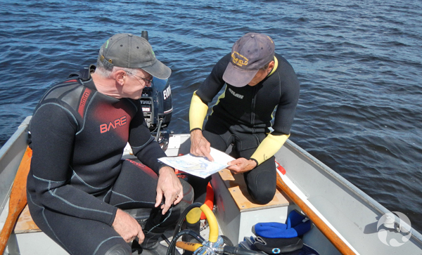 Two male divers seated in a boat study a map.