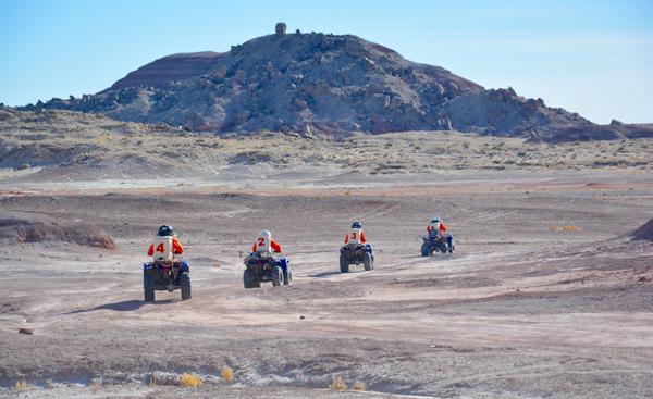 Four people ride ATV's into the desert.