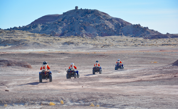 Four people ride ATV's into the desert.