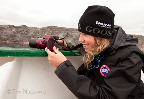 Alana Krug-Macleod holds a camera while leaning on the side of a ship during a journey with Students on Ice.
