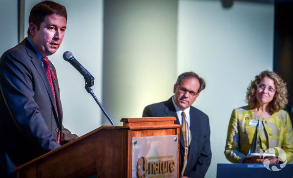 Winner Hugo d'Amours, with Cascades Inc., speaks at podium as Meg Beckel and presenter Ivan Semeniuk look on.