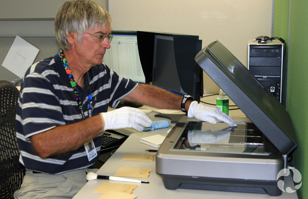 A man sits at a desk using a scanner.