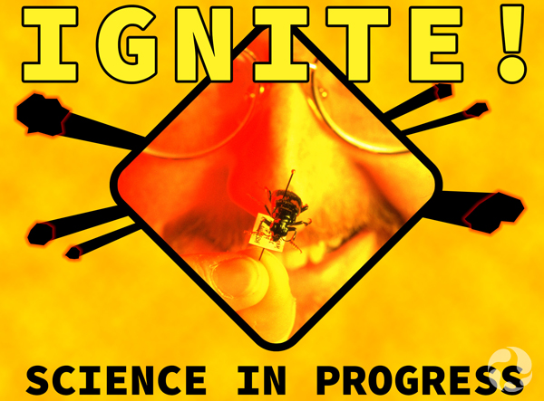 A sign that says IGNITE – Danger: Science in progress, with a pinned insect and part of a man's face behind it.