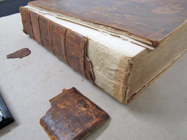 A damaged book on a table, next to leather binding pieces.