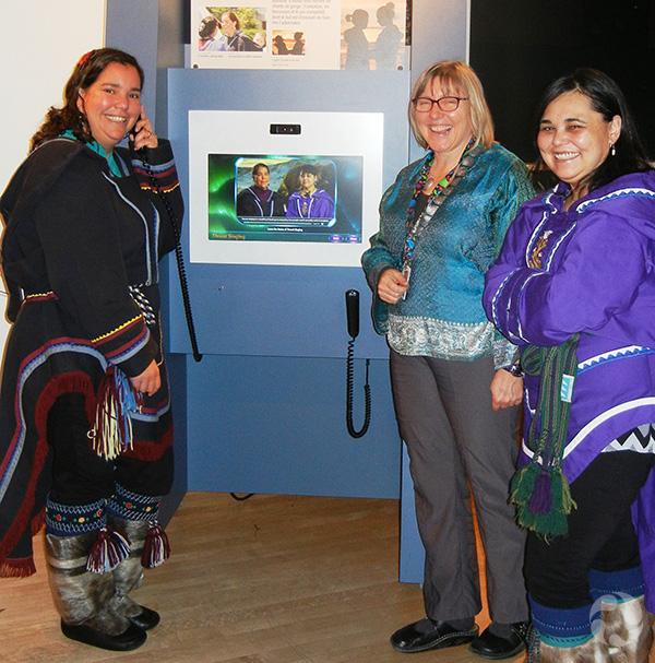 Three women stand beside the throat-singing kiosk.