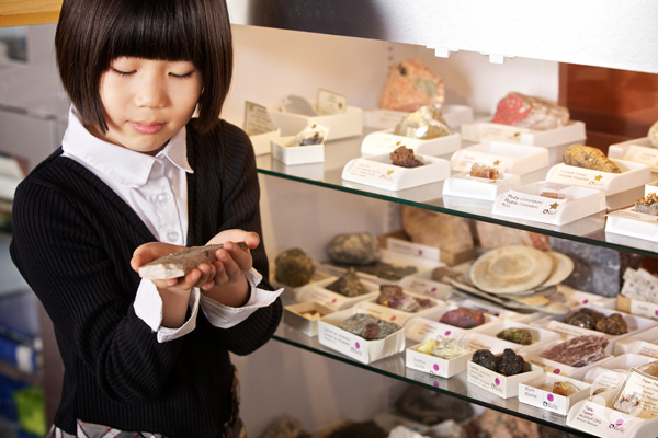 A child holds a specimen in front of a cabinet containing rocks and minerals.