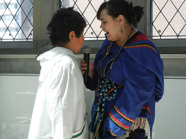A pair of museum visitors face each other; one holds a microphone.