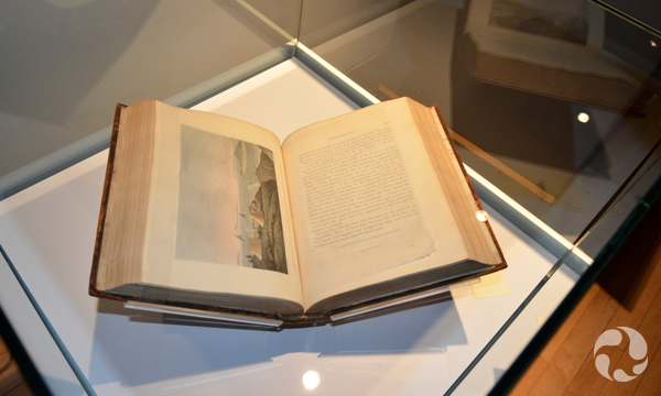 A display case containing a book open to an illustrated page.
