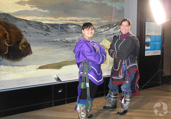 Two women in traditional outerwear stand in front of a diorama.