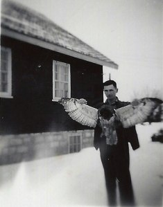 A man spreads the wings of a dead bird.