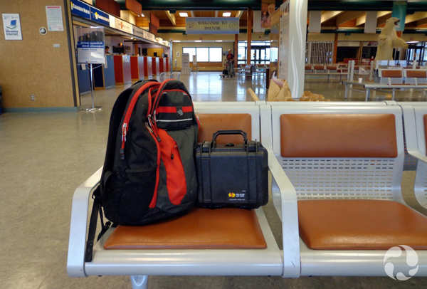 A row of seats with a knapsack and a rigid carrying case.