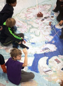 Students sitting on the Arctic floor map