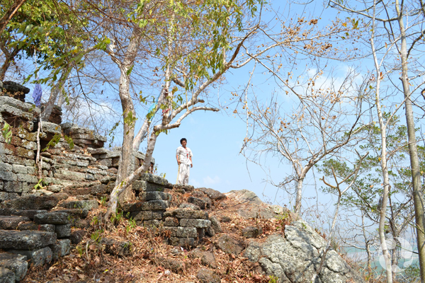 A person stands on a rocky outcrop with stone stairs.