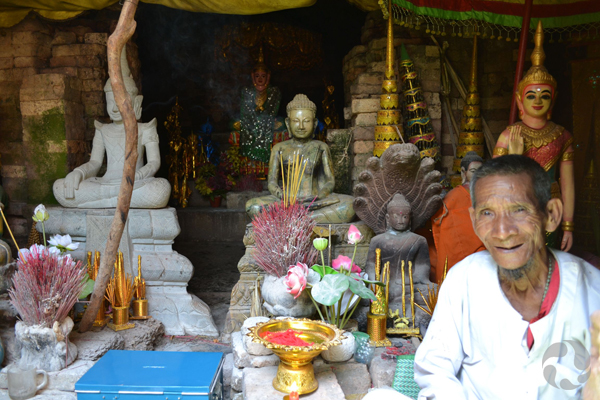 A man sits in front of statues and offerings.