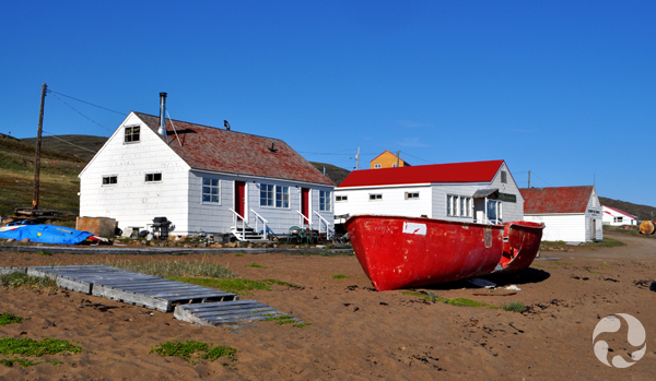 A beached boat rests in front of several small white buildings.