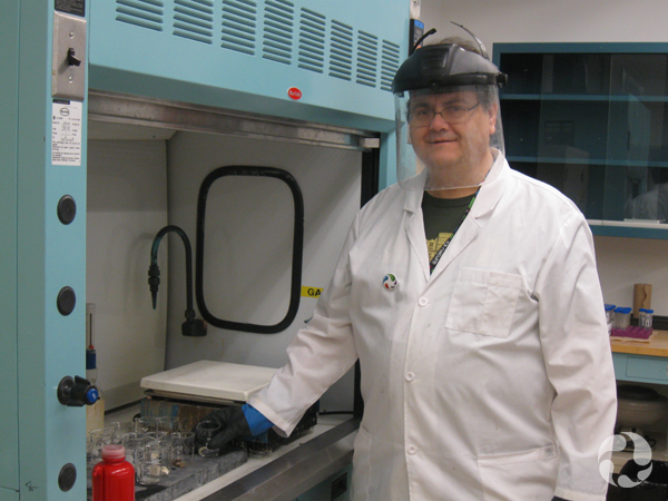 A man wearing protective gear stands in a laboratory.
