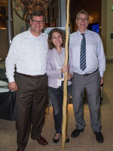 Three people pose together, one holding a narwhal tusk.