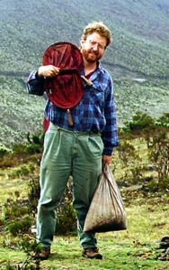 Bob Anderson in a hilly landscape, holding collecting equipment.