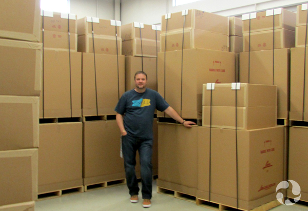 A man stands beside towering ranges of stacked boxes.