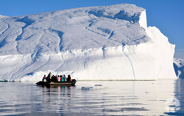 Several people in a boat in front of an iceberg.