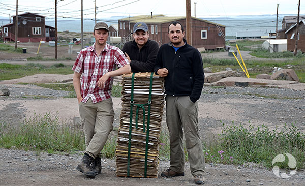 Three men stand around a full plant press.
