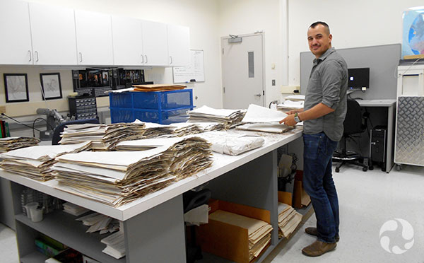 A man stands at a table piled with herbarium sheets.