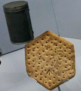 A biscuit and a canister in a display case.