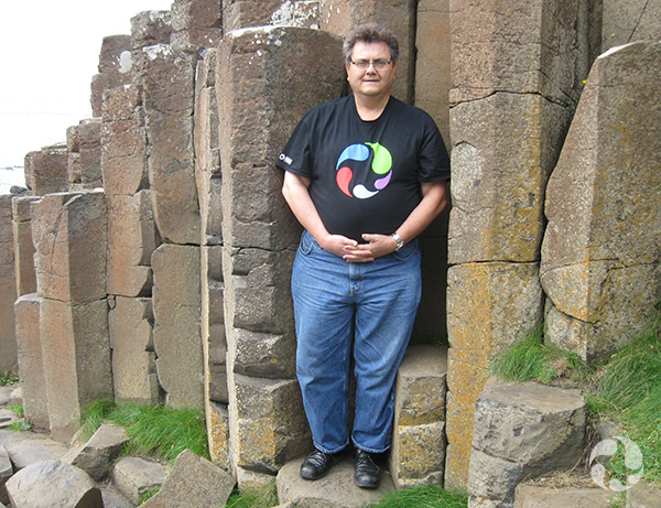 A man stands next to basalt columns.